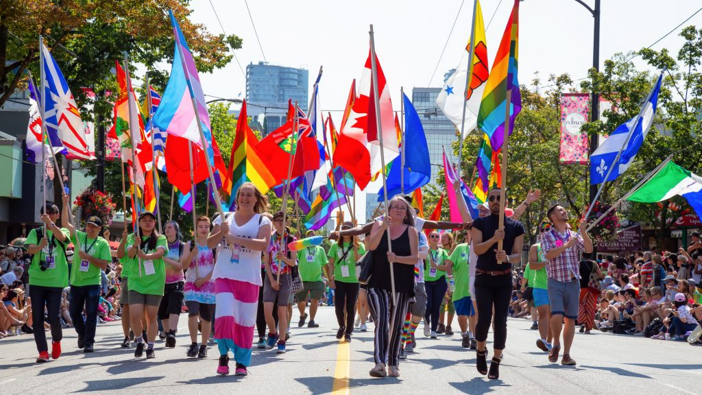 People marching in a Pride parade in downtown Vancouver and carrying the pride flag, trans flag, Canada flag, and flags of Canadian provinces and territories.