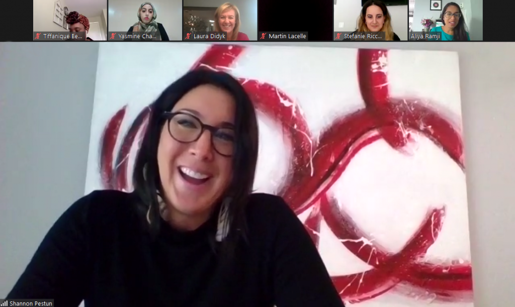 A screenshot of Shannon Pestun smiling during the webinar and sitting in front of an abstract art piece with images of other webinar participants in a row at the top of the screen
