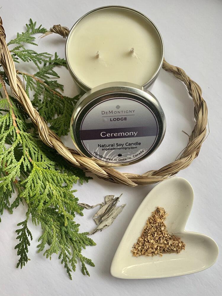 Une boîte argentée ouverte contenant une bougie de soya de couleur crème placée à côté de branches de cèdre, de la ficelle tissée et un plat de couleur crème en forme de cœur contenant des herbes.
