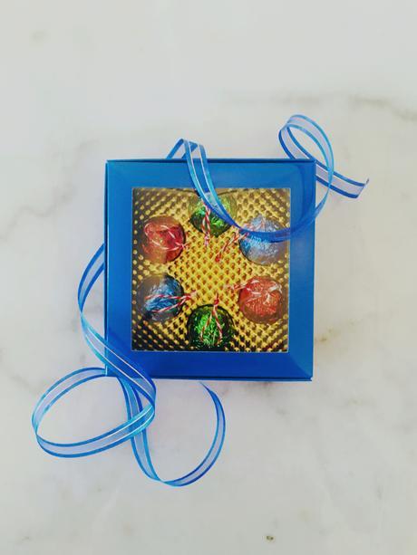 Une boîte et un ruban bleu royal avec des chocolats aux couleurs festives.