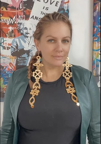 Blonde woman wearing a dark grey top, pale green leather jacket and very long, ornate gold earrings looking straight into the camera with colourful artwork behind her.