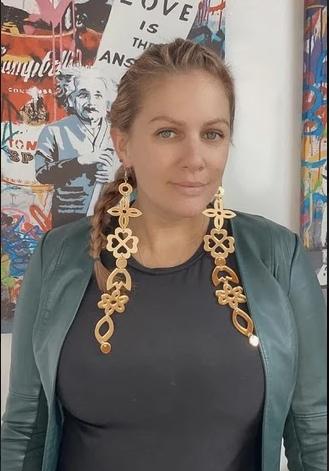 Femme blonde vêtue d'un haut gris foncé et d'une veste en cuir vert pâle; elle porte de très longues boucles d'oreilles en or ouvragées et regarde directement dans l'appareil photo. On peut voir des illustrations colorées derrière elle.