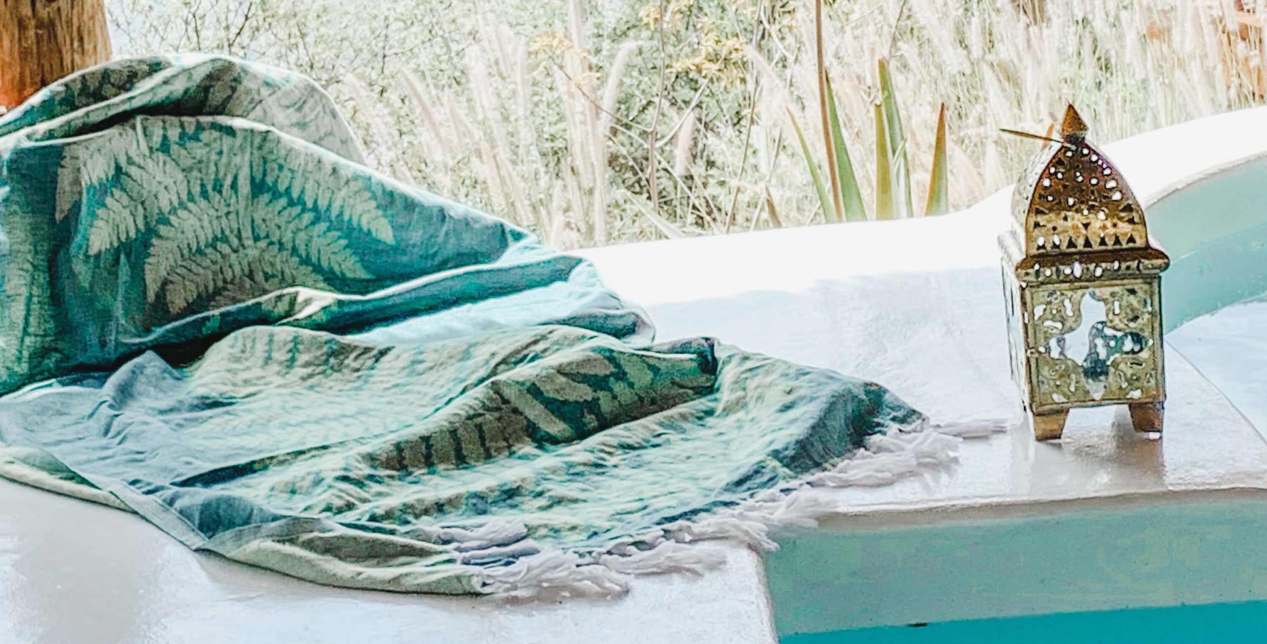 A light turquoise, Turkish woven blanket with cream coloured fern print and long tassel fringe laid upon the edge of a bath with a Turkish bronze lantern.