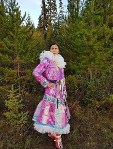 Indigenous woman wearing a long, bright, multi-coloured patchwork parka and red mukluks looking into the distance in the forest.