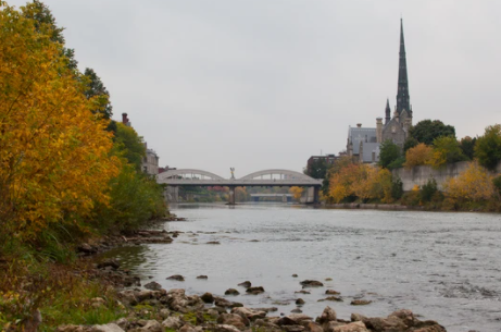 A dark grey church on the horizon on the right, arched bridge in the middle with the river flowing underneath, surrounded by yellow and green foliage on the embankments.