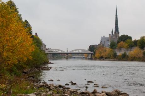 Une église gris foncé à l'horizon à droite, un pont en arc au centre, la rivière coulant en dessous, entourée de feuillage jaune et vert sur les remblais.