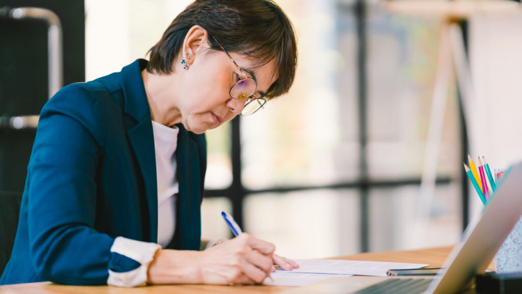 Portrait of a woman in a blue blazer sitting at a desk and writing on a piece of paper with a laptop in the foreground