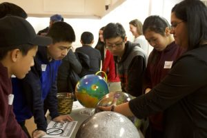 Group of students surrounding table with Dr. Shankar teaching and referring to globes on a table.